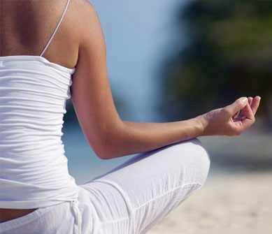 Female meditating at the beach to find her happy new you.