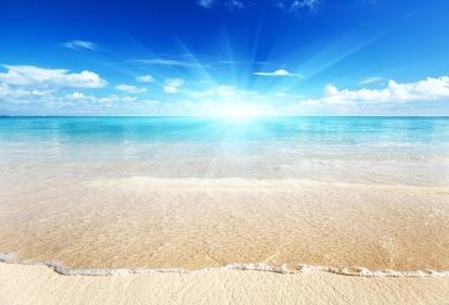 Beautiful, bright sun rising over the ocean at the beach.